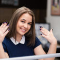 Happy young woman with her nails done at cosmetic parlor